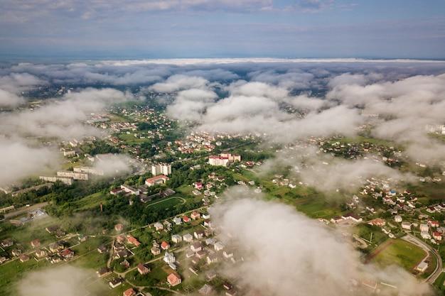 Vista aérea de nuvens brancas acima de uma cidade ou vila com fileiras de edifícios e ruas curvas entre campos verdes no verão.