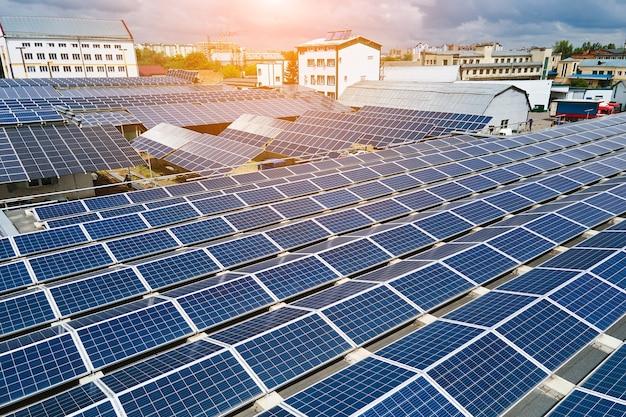 Vista aérea de painéis solares fotovoltaicos azuis montados no telhado de um prédio industrial para a produção de eletricidade ecológica verde. produção do conceito de energia sustentável.