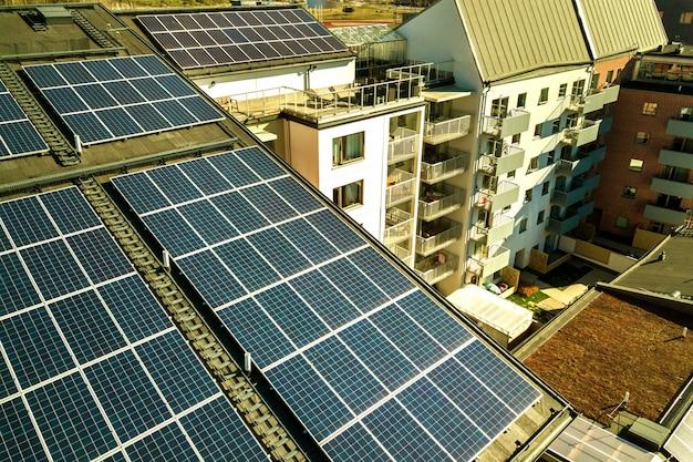 Vista aérea de painéis solares fotovoltaicos em uma parte superior do telhado do bloco de construção residencial para a produção de energia elétrica limpa. conceito de habitação autônoma.