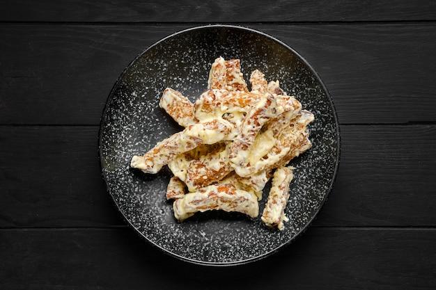 Vista aérea de palitos de pão salgado cobertos com queijo derretido em um prato