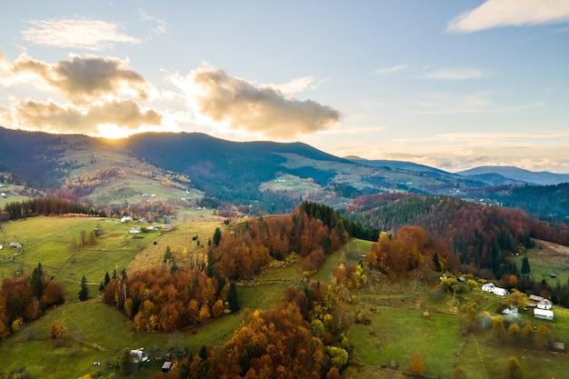 Vista aérea de pequenas casas de pastor em pastagens largas entre a floresta de outono nas montanhas dos cárpatos ucranianos ao pôr do sol.