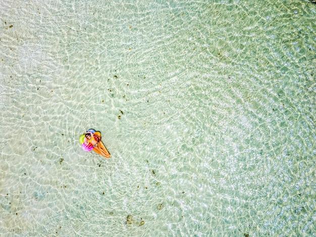 Vista aérea de pessoas em férias de verão com uma linda garota em lilo moderno colorido relaxando e tomando banho de sol na água da praia de lagoa do oceano verde claro