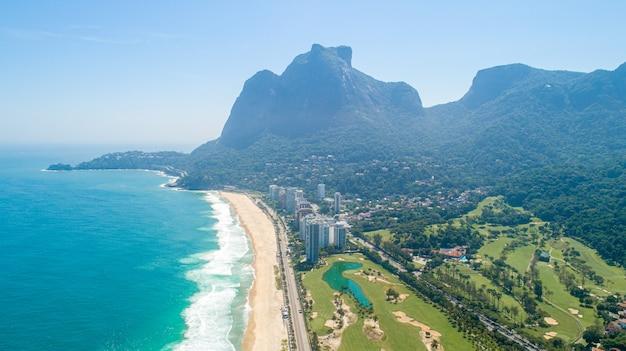 Vista aérea de praia tropical. ondas quebram na praia tropical de areia amarela. rio de janeiro, brasil