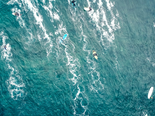 Vista aérea de surfistas nas águas azuis do fundo do oceano atlântico