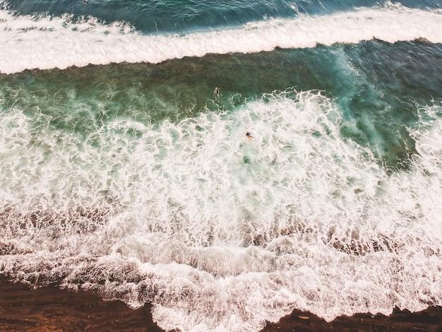 Vista aérea de surfistas nas ondas do oceano atlântico. praia de areia