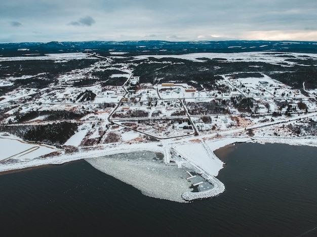 Vista aérea de terreno nevado perto do mar