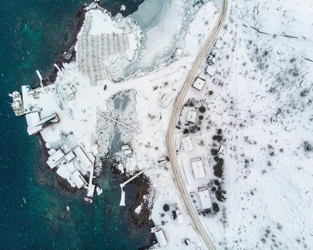 Vista aérea de topo da estrada com cais no litoral e oceano ártico no inverno