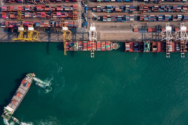 Vista aérea de topo do porto de embarque para importação internacional, exportação, logística de carga, transporte, serviços empresariais e indústria e pequeno rebocador arrastar contêineres
