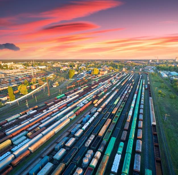 Vista aérea de trens de carga coloridos na estação ferroviária ao pôr do sol