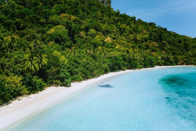 Vista aérea de um barco atracado em uma praia isolada de areia branca com águas azul-turquesa e coqueiros
