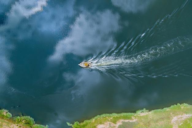 Vista aérea de um barco de luxo flutuante no oceano azul na vista de alta altitude