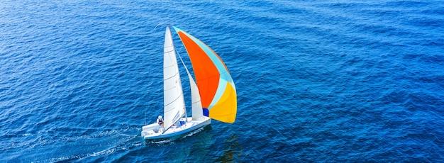 Vista aérea de um belo iate à vela branco com uma vela colorida.