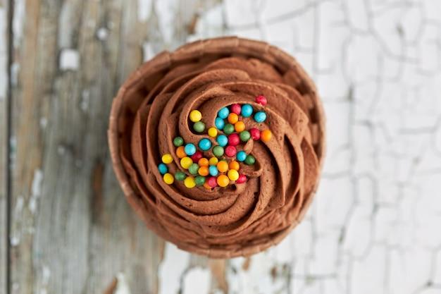 Vista aérea de um bolinho de chocolate com doces coloridos.