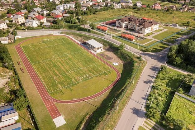 Vista aérea de um campo de futebol em um estádio coberto com grama verde na área da cidade rural.