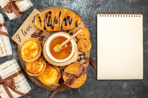 Vista aérea de um delicioso café da manhã com panquecas de croissant, cookies empilhados, querida, lindo presente para sua amada e caderno espiral em fundo escuro