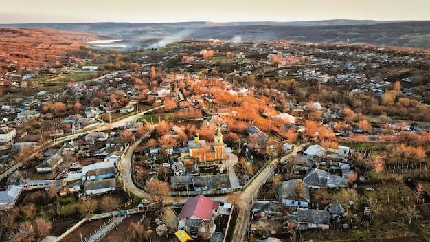Vista aérea de um drone de uma vila na moldávia ao pôr do sol. igreja de edifícios residenciais antigos