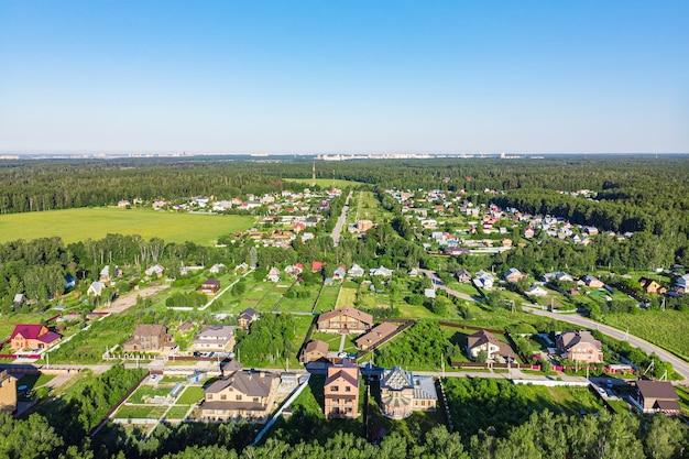 Vista aérea de um drone de uma vila rural, campos e florestas ao redor