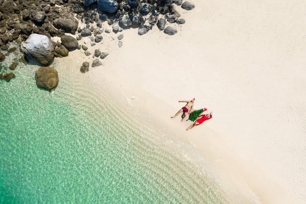 Vista aérea de um jovem casal deitado na areia