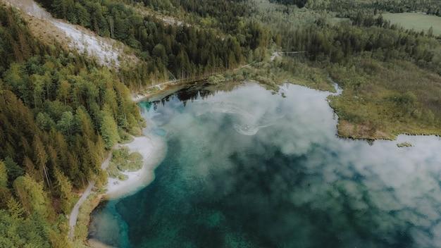 Vista aérea de um lago cercado por florestas com o céu nublado refletindo na água