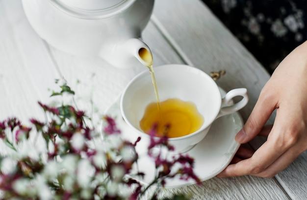 Vista aérea, de, um, mulher, despejar, um, chá quente, bebida