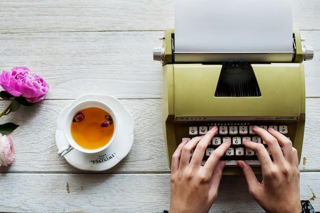 Vista aérea, de, um, mulher, digitando, ligado, um, retro, typewriter, em branco, papel