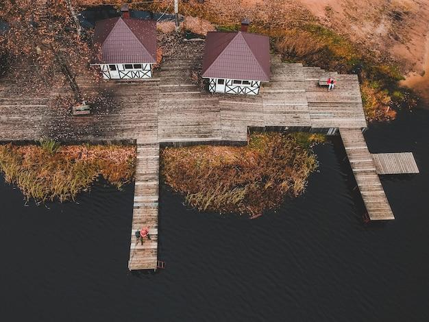 Vista aérea de um pescador com uma vara de pescar no cais, margem do lago, floresta de outono. finlândia.
