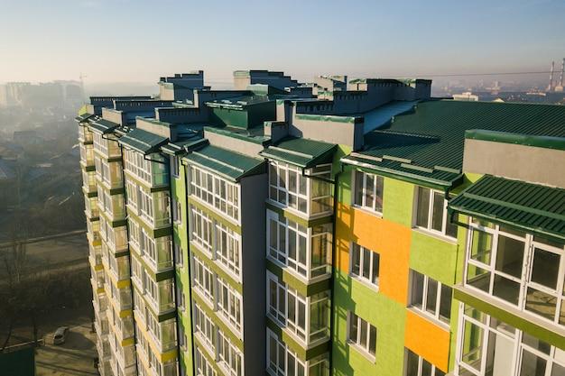 Vista aérea de um prédio alto de apartamentos residenciais com muitas janelas e varandas.