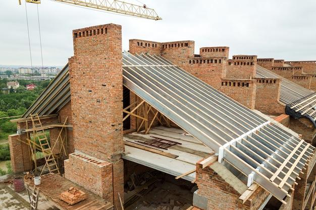 Vista aérea de um prédio inacabado de tijolos com estrutura de telhado de madeira em construção.