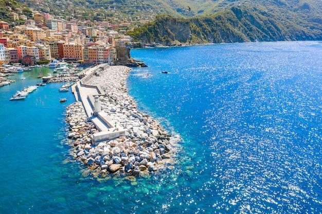 Vista aérea de um quebra-mar e um farol no mar da ligúria com montanha. camogli perto de gênova, itália. a água azul turquesa no mar lava a beira-mar.