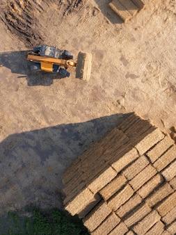 Vista aérea de um trator dobrando fardos de feno em um campo em um dia ensolarado de outono. foto do drone. vista do topo