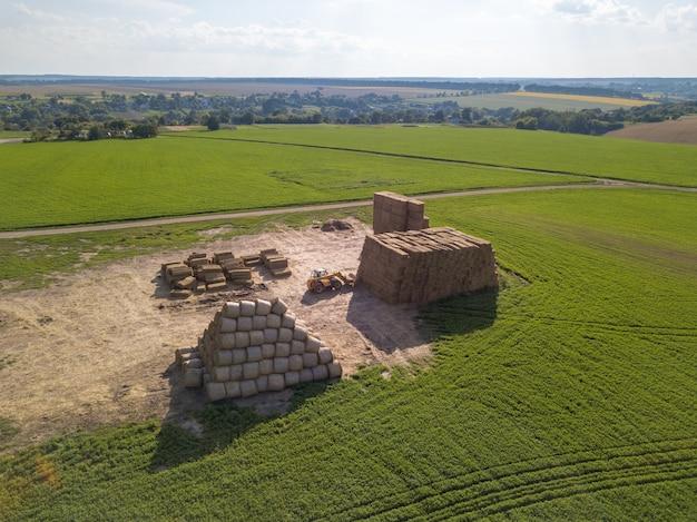 Vista aérea de um trator drone dobrando uma pilha de feno em pilhas em um campo verde em um dia ensolarado. conceito de agronegócio