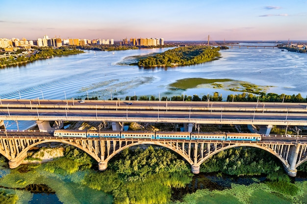 Vista aérea de um trem elétrico urbano de kiev cruzando o rio dnieper pela ponte darnytsia. ucrânia, europa oriental