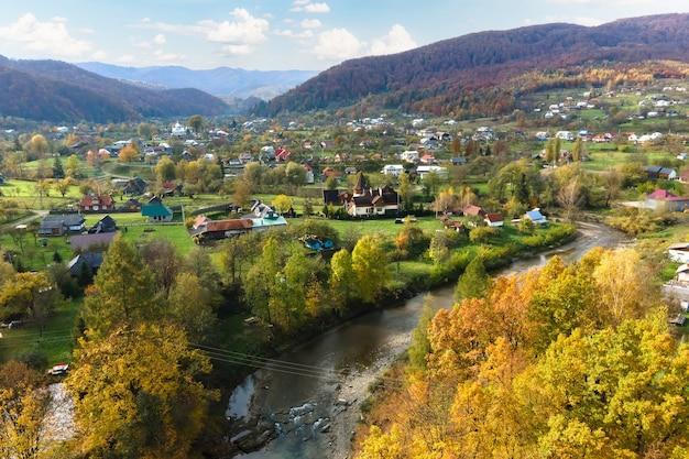 Vista aérea de uma área rural de aldeia com pequenas casas entre colinas de outono cobertas por floresta de abetos verdes e amarelos.