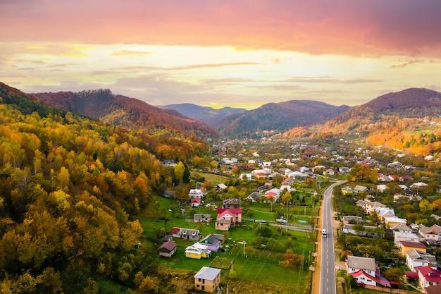Vista aérea de uma área rural de vila com pequenas casas entre colinas de outono cobertas com floresta de abetos verdes e amarelos ao pôr do sol.