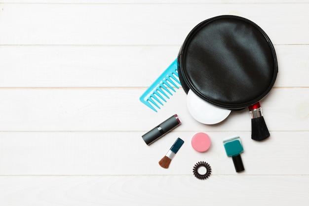 Vista aérea de uma bolsa de couro cosméticos com maquiagem produtos de beleza, derramando sobre madeira.