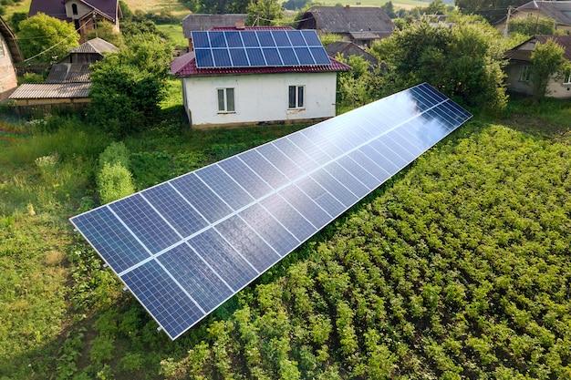 Vista aérea de uma casa com painéis solares azuis para energia limpa.
