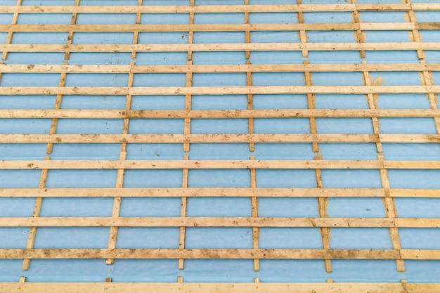 Vista aérea de uma casa de tijolos com estrutura de telhado de madeira em construção.