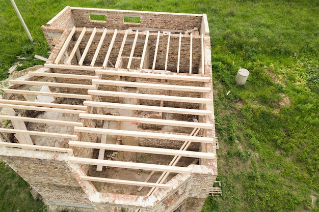 Vista aérea de uma casa de tijolos com moldura de teto de madeira em construção.