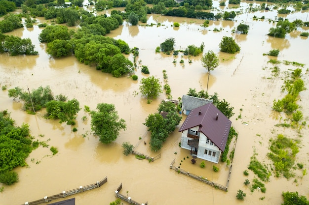 Vista aérea de uma casa inundada com água suja ao redor.