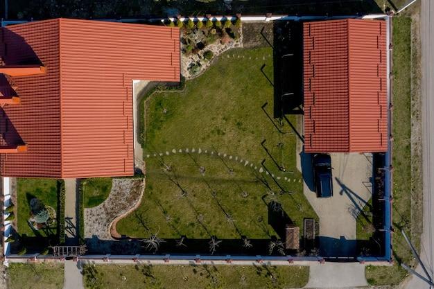 Vista aérea de uma casa particular com quintal pavimentado com gramado verde com piso de fundação de concreto.
