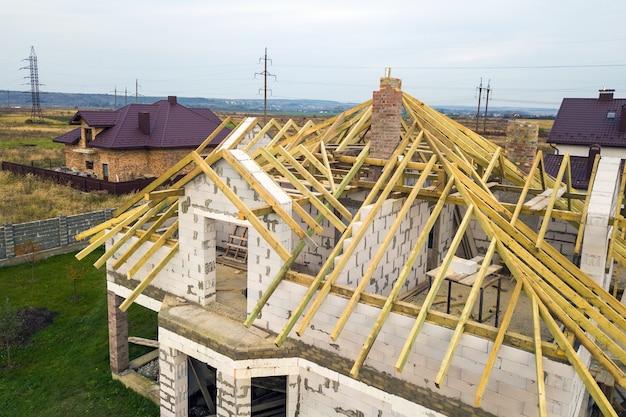 Vista aérea de uma casa privada com paredes de tijolos de concreto aerado e estrutura de madeira para telhado futuro.