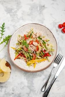 Vista aérea de uma deliciosa salada de frango com legumes, tomate e abacaxi seco, talheres em uma superfície branca manchada com espaço livre