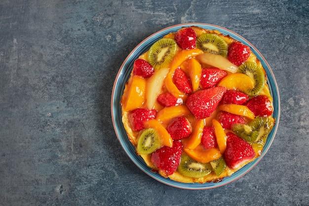 Vista aérea de uma deliciosa torta com creme e frutas frescas da estação.