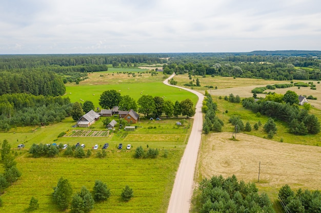 Vista aérea de uma estrada rural através de terras agrícolas e vilarejos
