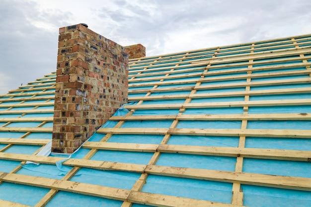 Vista aérea de uma estrutura de telhado de madeira de uma casa de tijolos em construção.