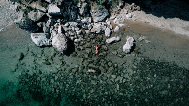 Vista aérea de uma garota na praia rochosa. férias e aventura. praia e água azul-turquesa. vista superior do zangão na praia, mar azul e relaxar garota. viajar e relaxar