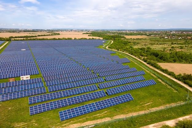 Vista aérea de uma grande usina elétrica sustentável com muitas fileiras de painéis solares fotovoltaicos para a produção de energia elétrica ecológica limpa. eletricidade renovável com conceito de emissão zero.