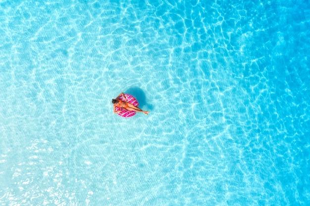 Vista aérea de uma jovem mulher nadando com anel de natação