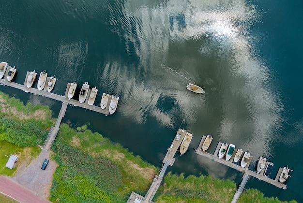 Vista aérea de uma lancha flutuando perto do cais da pequena plataforma de madeira no oceano de águas turquesas