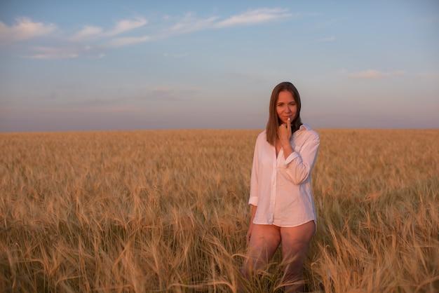 Vista aérea de uma mulher deitada no campo de trigo amarelo
